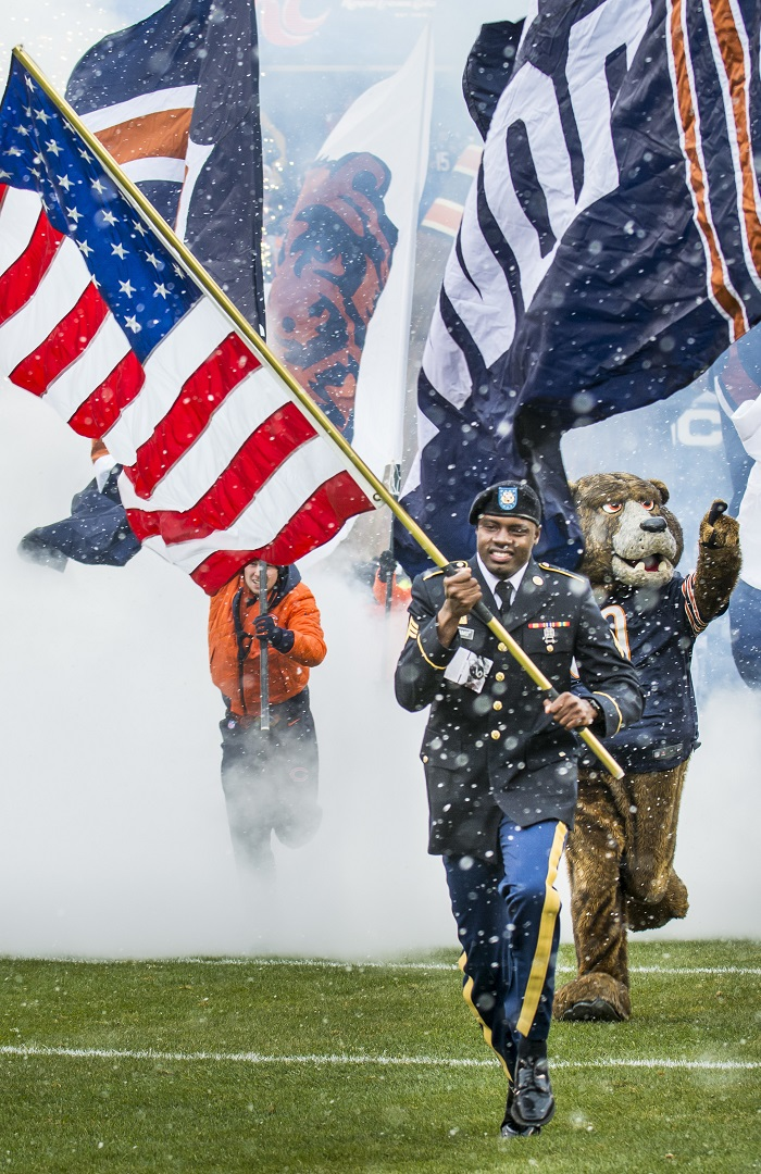 Sgt. Brian Abrams, Army Reserve Soldier with the 863rd Engineer Battalion, Forward Support Company, carries the American flag onto the field leading the Chicago Bears team members onto the field prior to kickoff during an NFL game designated to honor veterans and military service members at Soldier Field in Chicago, Nov. 16. (U.S. Army photo by Sgt. 1st Class Michel Sauret)